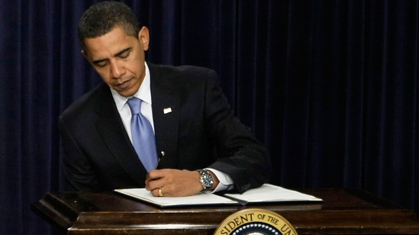 President Barack Obama signs executive orders during an event at the Eisenhower Executive Office Building of the White House.