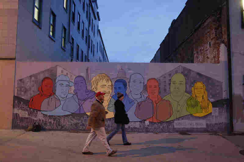 "People walk past a ""Homeless Lives Matter"" mural on D street in the early morning hours."