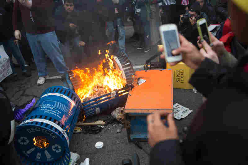 Spectators take photographs of a trash fire started by protesters on K Street.