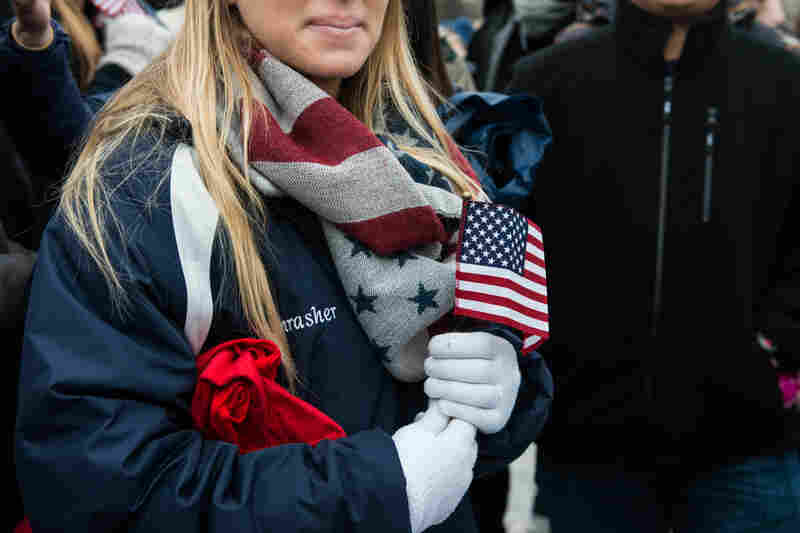 A woman clutches an American flag as she watches the crowd fill in the National Mall.