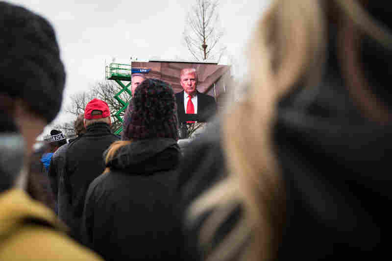 President Donald Trump is seen on a screen on the National Mall.