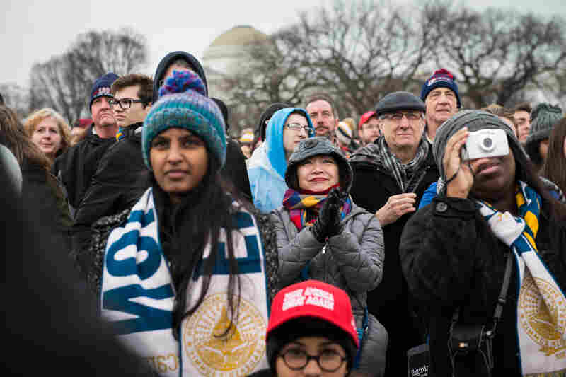 Crowds watch giant screens showing President Donald Trump being sworn into office.