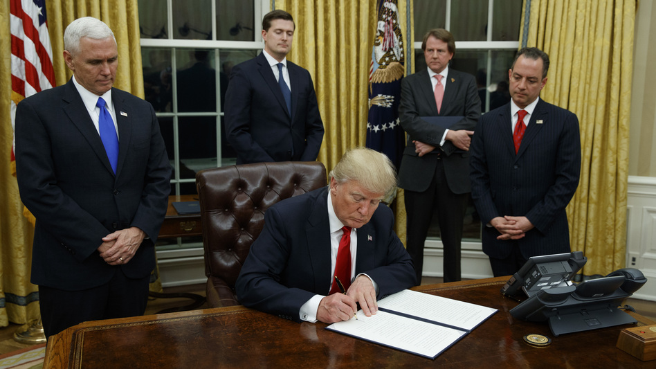 President Donald Trump, flanked by Vice President Mike Pence and Chief of Staff Reince Priebus, signs his first executive order on health care, on Friday. (Evan Vucci/AP)