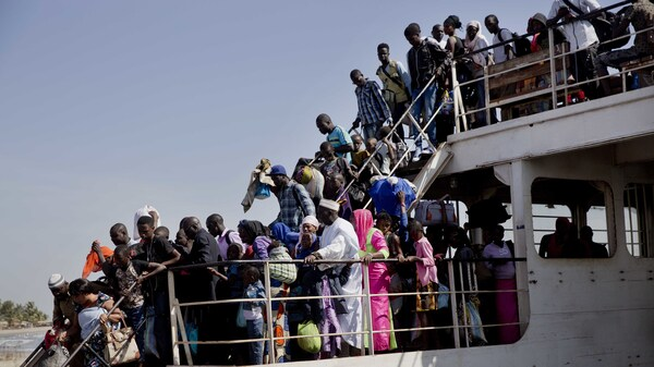 A ferry carrying people who fled Gambia arrives at the port in Banjul, Gambia, on Sunday.