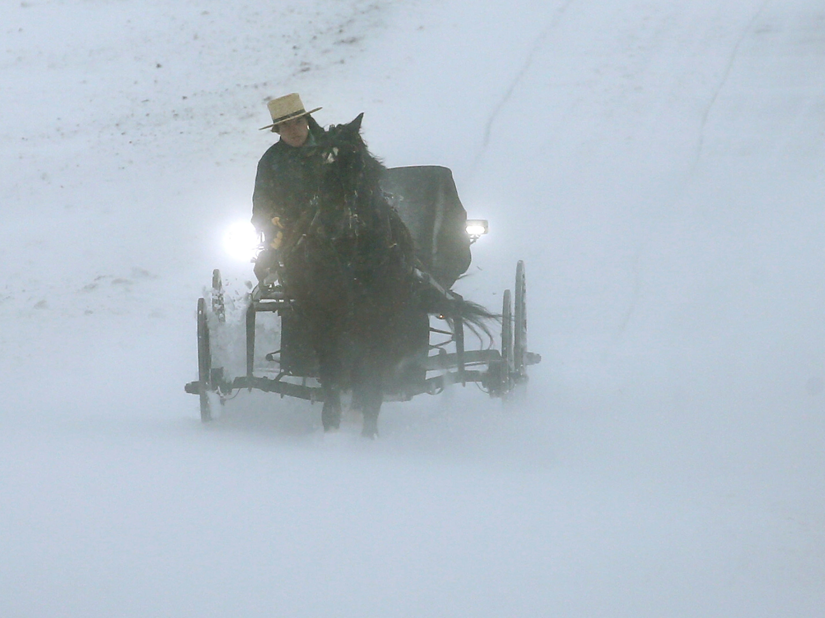 An Amish man drives his buggy through heavy snow and wind on Monday in Mechanicsville, Md. (Mark Wilson/Getty Images)