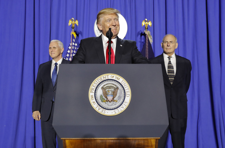 President Trump, accompanied by Vice President Pence (left) and Homeland Security Secretary John F. Kelly, pauses while speaking at the Department of Homeland Security. (Pablo Martinez Monsivais/AP)