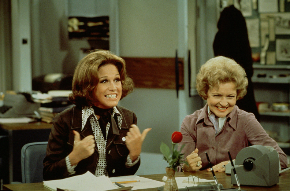Mary Tyler Moore (left, as Mary Richards) gives a 'thumbs up' sign as she sits at her desk with Betty White (as Sue Ann Nivens) in a scene from 'The Mary Tyler Moore Show' in 1975. (CBS Photo Archive/Getty Images)