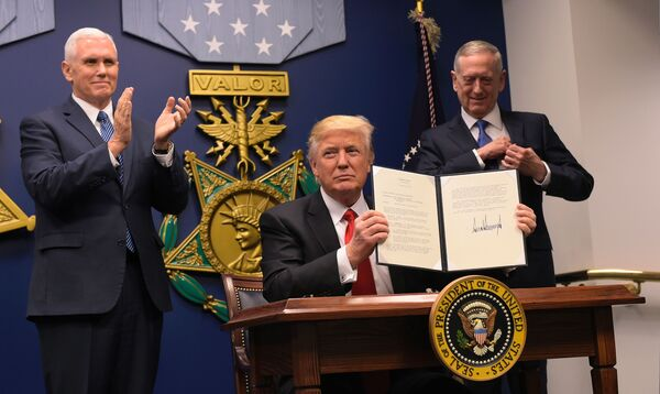 President Trump displays executive actions he has signed alongside Defense Secretary James Mattis and Vice President Pence on Friday at the Pentagon in Washington, D.C.