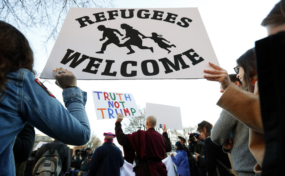 Protesters hold signs near the White House during a protest about President Trump's immigration policies on Wednesday. A proposed presidential action would freeze immigration from seven mostly Muslim countries for security reasons. But the list does not include any of the countries whose nationals have killed Americans in the U.S. since Sept. 11, 2001. (Alex Brandon/AP)