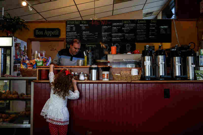 MaKinnley Craig, 4, reaches for a spoon at Ane Mae's, while shop owner Terry Trout works behind the counter.