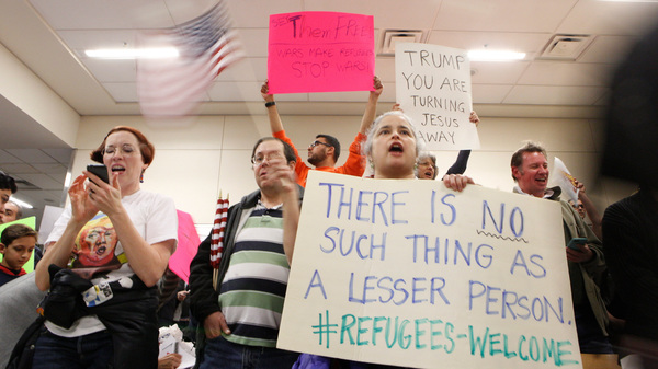 Protesters gather at Dallas-Fort Worth International Airport to denounce President Trump's executive order that bans certain immigration.