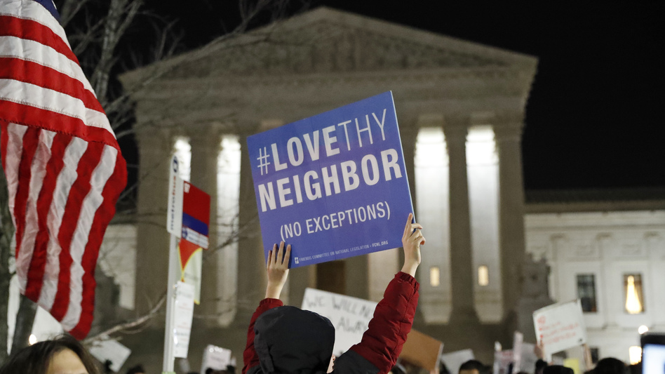 A protester carries a sign in front of the Supreme Court during a protest about President Trump's recent executive orders on Monday in Washington, D.C. (Alex Brandon/AP)