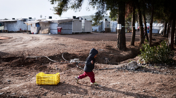 A child drags a crate at a refugee camp for Syrians and Kurds north of Athens. Children under age 14 make up nearly half of the Syrian refugees resettled in the U.S.
