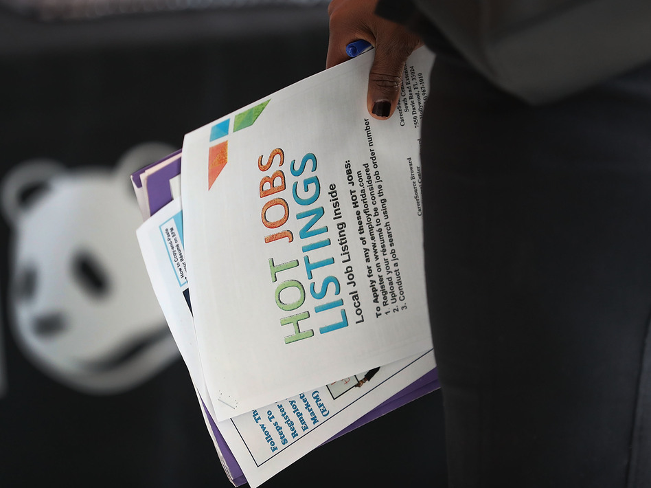 A woman holds a pamphlet announcing jobs listings during the JobNewsUSA job fair at the BB&T Center in Sunrise, Fla., in November 2016. (Joe Raedle/Getty Images)