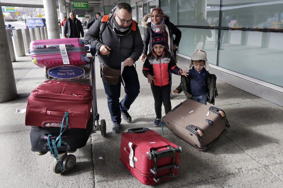 Munther Alaskry, accompanied by his wife, Hiba; son, Hassan; and daughter, Dima, gather their luggage as they leave JFK International Airport in New York on Feb. 3. Alaskry and his family arrived after the Trump administration reversed course and said he and other interpreters who had supported the U.S. military could come to America. (Richard Drew/AP)