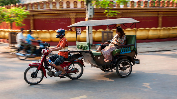 A tuk-tuk speeds past down an urban Cambodian road. One deportee used his English language skills — and sense of humor — to build a successful tuk-tuk tour business.
