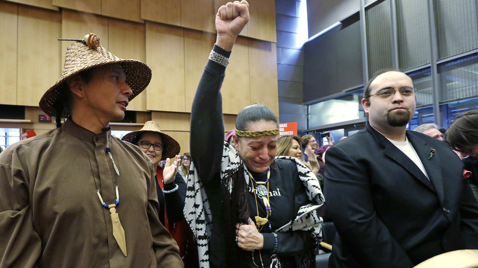 Olivia One Feather (center) of the Standing Rock Sioux tribe holds up her fist after the Seattle City Council voted Tuesday to divest from Wells Fargo over its role as a lender to the Dakota Access Pipeline project. (Elaine Thompson/AP)