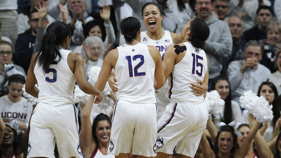 Connecticut's Napheesa Collier, (center) celebrates with teammates (from left) Crystal Dangerfield, Saniya Chong and Gabby Williams in Storrs, Conn., after beating South Carolina 66-55 — the Huskies' 100th win. (Jessica Hill/AP)
