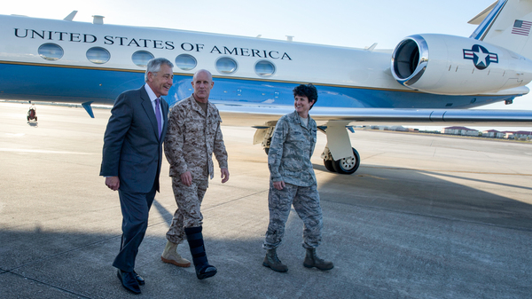 U.S. Secretary of Defense Chuck Hagel, left, walks with Vice Adm. Robert Harward, center, the deputy commander of U.S. Central Command, and Col. Kelly Martin, the vice commander of 6th Air Mobility Wing, after landing at MacDill Air Force Base, Tampa, Fla., March 21, 2013.