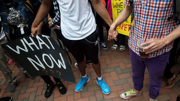 Uncertainty about the future can raise stress levels, psychologists say. Here, students in Charlotte, N.C., hold hands during a Sept. 21 protest after Keith Lamont Scott was shot and killed by a police officer.