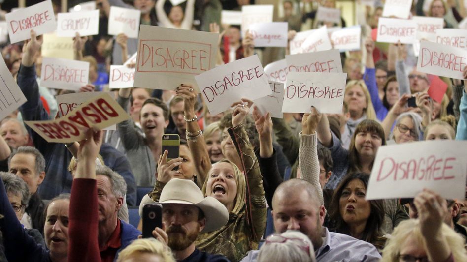 People react to Rep. Jason Chaffetz as he speaks during a town hall meeting at Brighton High School in Utah last week.