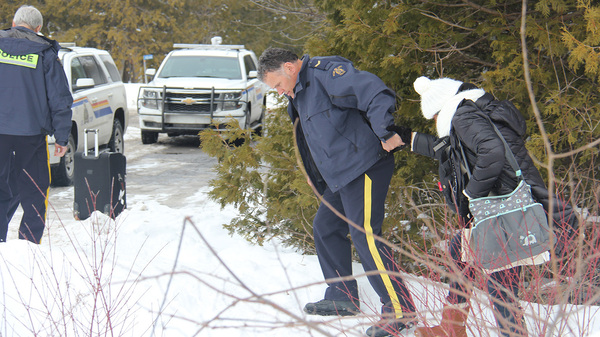 A Canadian police officer offers a hand to a migrant crossing the U.S.-Canada border near Champlain, N.Y. on Wednesday. The Royal Canadian Mounted Police are reporting surges in illegal crossings in Canada in recent months.