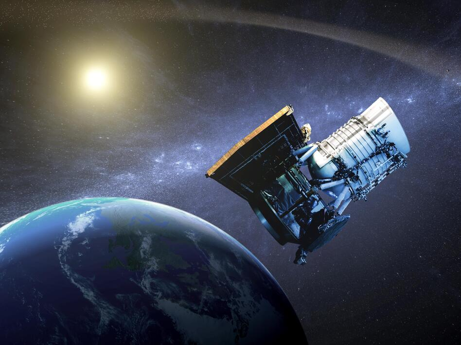An artist's concept shows the WISE spacecraft in its orbit around Earth.