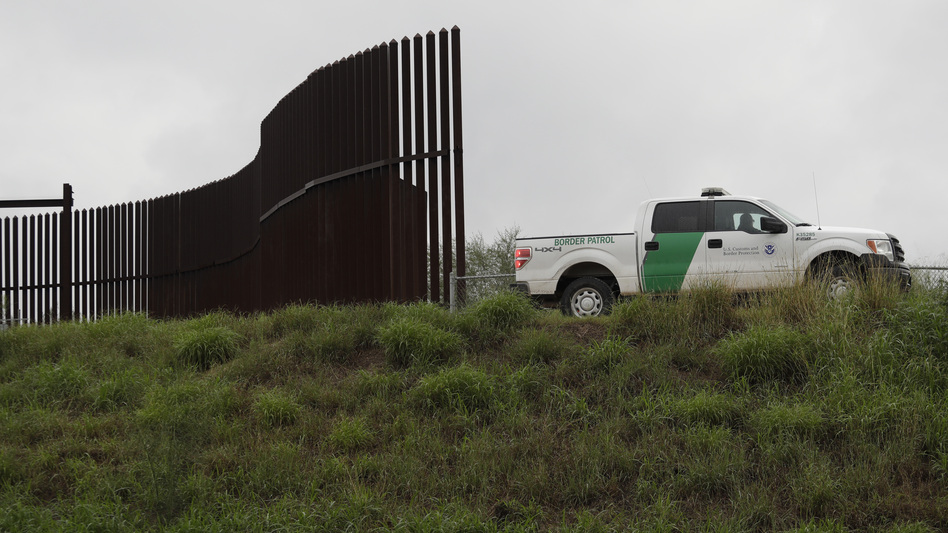 A U.S. Customs and Border Patrol agent passes along a section of border wall in Hidalgo, Texas. (Eric Gay/AP)