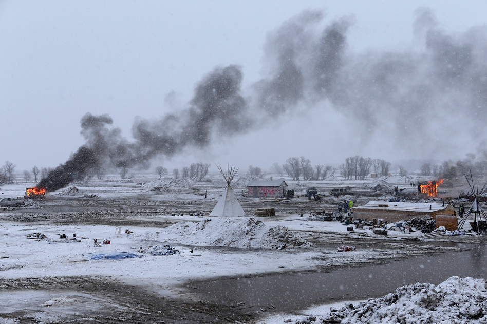 Snow falls on the Oceti Sakowin camp on Wednesday as structures smolder. (Angus Mordant for NPR)
