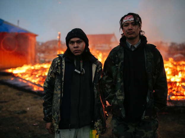 Chanse Zavalla, 22, left, and O'Shea Spencer, 20, right, stand in front of the remains of a hogan structure, set on fire ahead of the Army Corp's deadline to leave the Oceti Sakowin protest camp on February 22, 2017 in Cannon Ball, North Dakota.