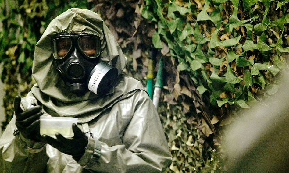 An instructor at Fort Leonard Wood, Mo., carries VX nerve agent inside a special chamber used for training in 2003. (Brendan Smialowski/Getty Images)