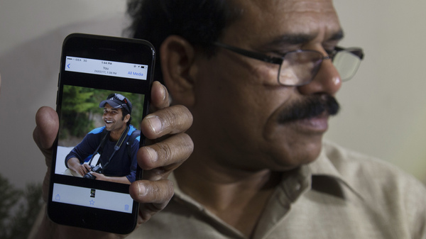 A man shows a cellphone picture of Alok Madasani, an engineer who was injured in Wednesday