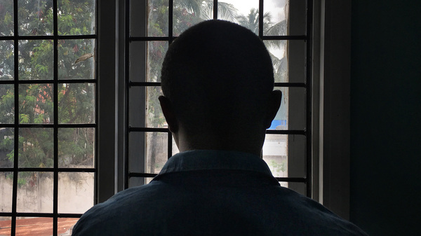 A gay man with HIV stands in a clinic in Dar es Salaam, Tanzania. He