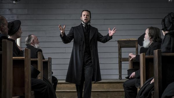 The Spite of the Hunter: Villainous preacher Guy Pearce excoriates his flock in Brimstone.
