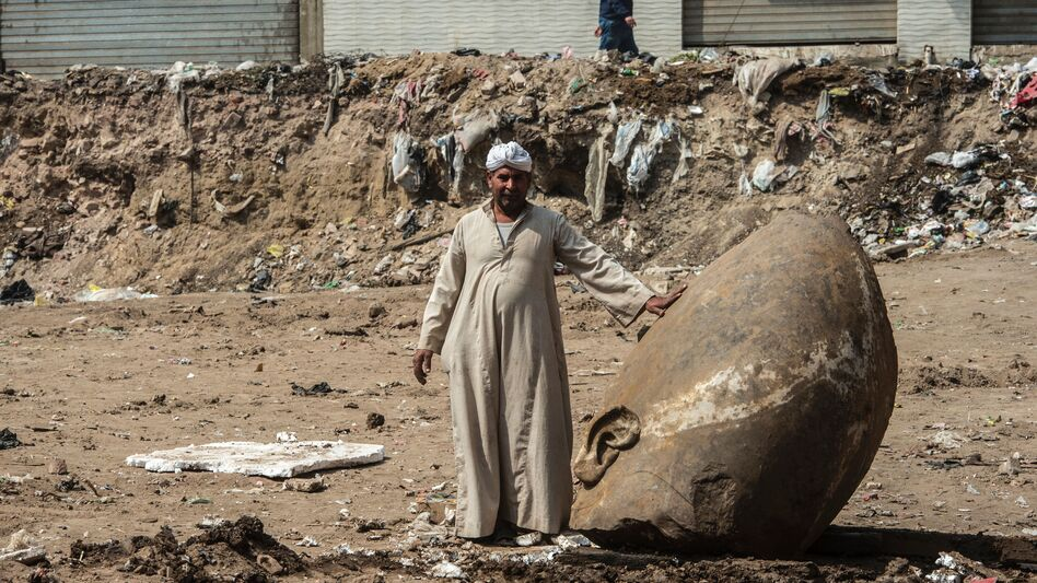 An Egyptian worker stands next to the head of a statue at the site of a new discovery by a team of German-Egyptian archaeologists in Cairo's Matariya District.