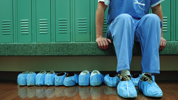 Medical worker in scrubs, sitting in a locker room.