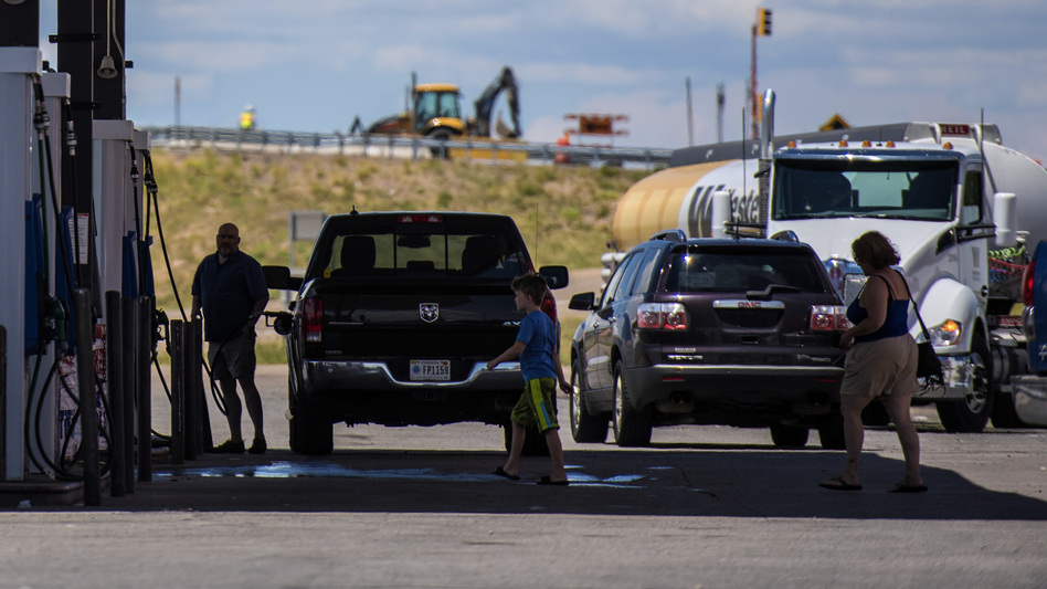 The CAFE standards that set fuel efficiency marks for the auto industry will be reopened for review, the Trump administration says. Here, vehicles refuel at a roadside gas station in New Mexico. (Bloomberg via Getty Images)