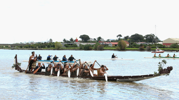 Māori paddlers guide a boat down the Whanganui River in New Zealand, during a visit from Britain