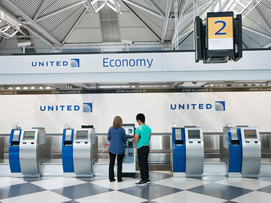 "Passengers check in for flights with United Airlines at Chicago O'Hare International Airport. United, American and Delta now offer no-frills ""basic economy"" fares. (Scott Olson/Getty Images)"
