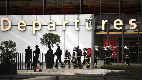 French firefighters and police officers secure Orly airport outside Paris on Saturday following the shooting of a man by French security forces. The attacker was known to French authorities, and his home had been searched following attacks in 2015.