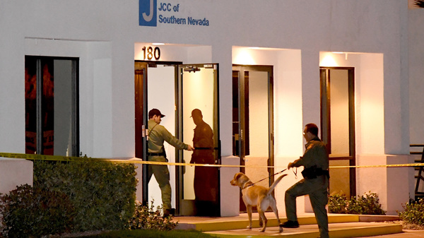 Las Vegas Metropolitan Police Department K-9 officers search the Jewish Community Center of Southern Nevada after an employee received a suspicious phone call that led about 10 people to evacuate the building on Feb. 27. A suspect in Israel has been arrested in connection with the waves of bomb threats like this one.