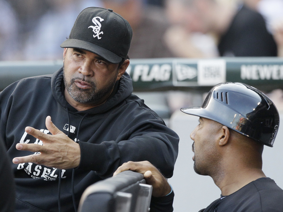 Chicago White Sox manager Ozzie Guillen, left, talks with first base coach Harold Baines in the dugout during a game in 2011. (Nam Y. Huh/AP)