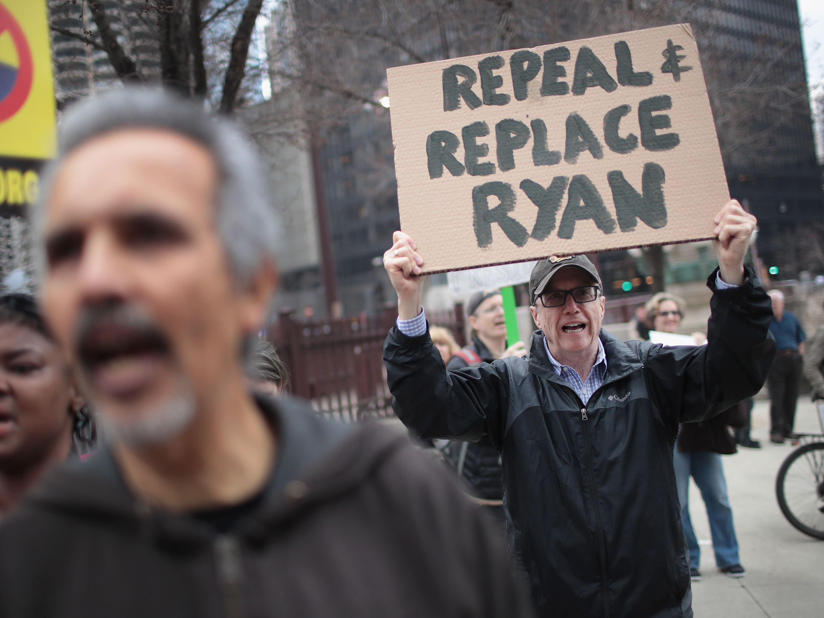 Demonstrators gather near Trump Tower after the defeat of the GOP health care plan. One man holds up a sign, urging the ouster of House Speaker Paul Ryan, who spearheaded the failed effort. (Scott Olson/Getty Images)