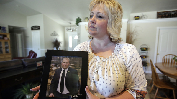 """Laurie Holt holds a photograph of her son Joshua Holt, who has been jailed in Venezuela, at her home in Riverton, Utah. """"Eventually,"""" she says, """"he"""