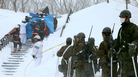 Firefighters carry a survivor they rescued from the site of an avalanche Monday in Nasu, Japan, as Self Defense Force personnel look on. Eight high school students are feared dead after an avalanche swept down on their mountain-climbing trip.