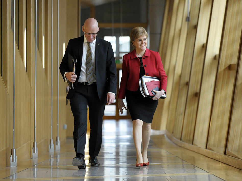 Scottish First Minister Nicola Sturgeon and Deputy First Minister John Swinney arrive at Scottish Parliament on Tuesday. They attended the second day of debate on a motion that ultimately granted Sturgeon the authority to pursue an independence referendum. (Andy Buchanan/AFP/Getty Images)