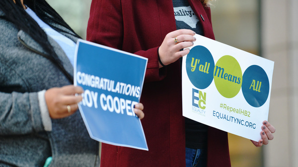 Roy Cooper supporters and those advocating to repeal the controversial HB2 bill hold signs in Charlotte on Dec. 7.