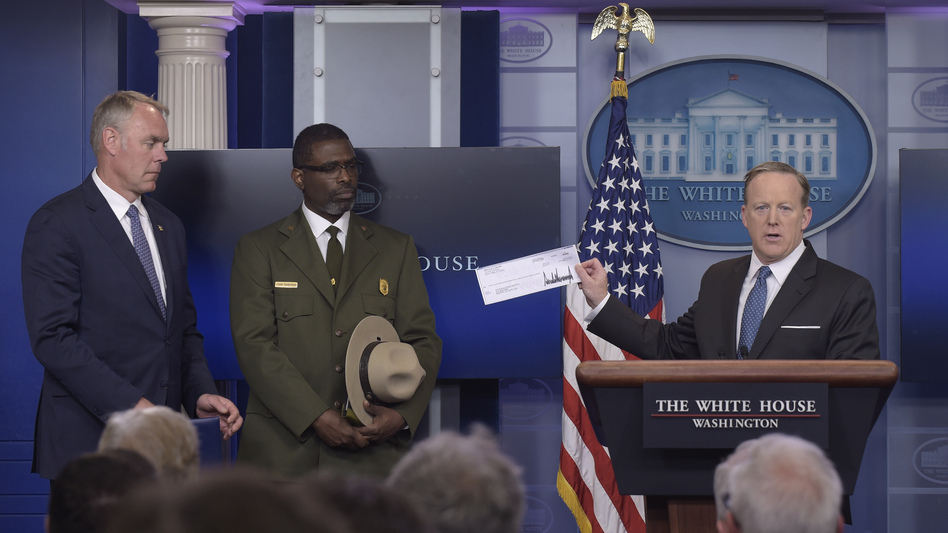 White House press secretary Sean Spicer holds up a check during the daily briefing at the White House on Monday with Interior Secretary Ryan Zinke, left, and Harpers Ferry park superintendent Tyrone Brandyburg. (Susan Walsh/AP)