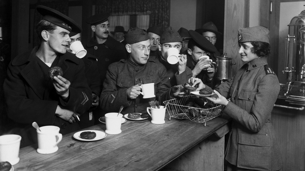 "American servicemen enjoy a hot cup of coffee at a Salvation Army hut in New York, circa 1918. During World War I, instant coffee was a key provision for soldiers on the front. They called it a ""cup of George."""