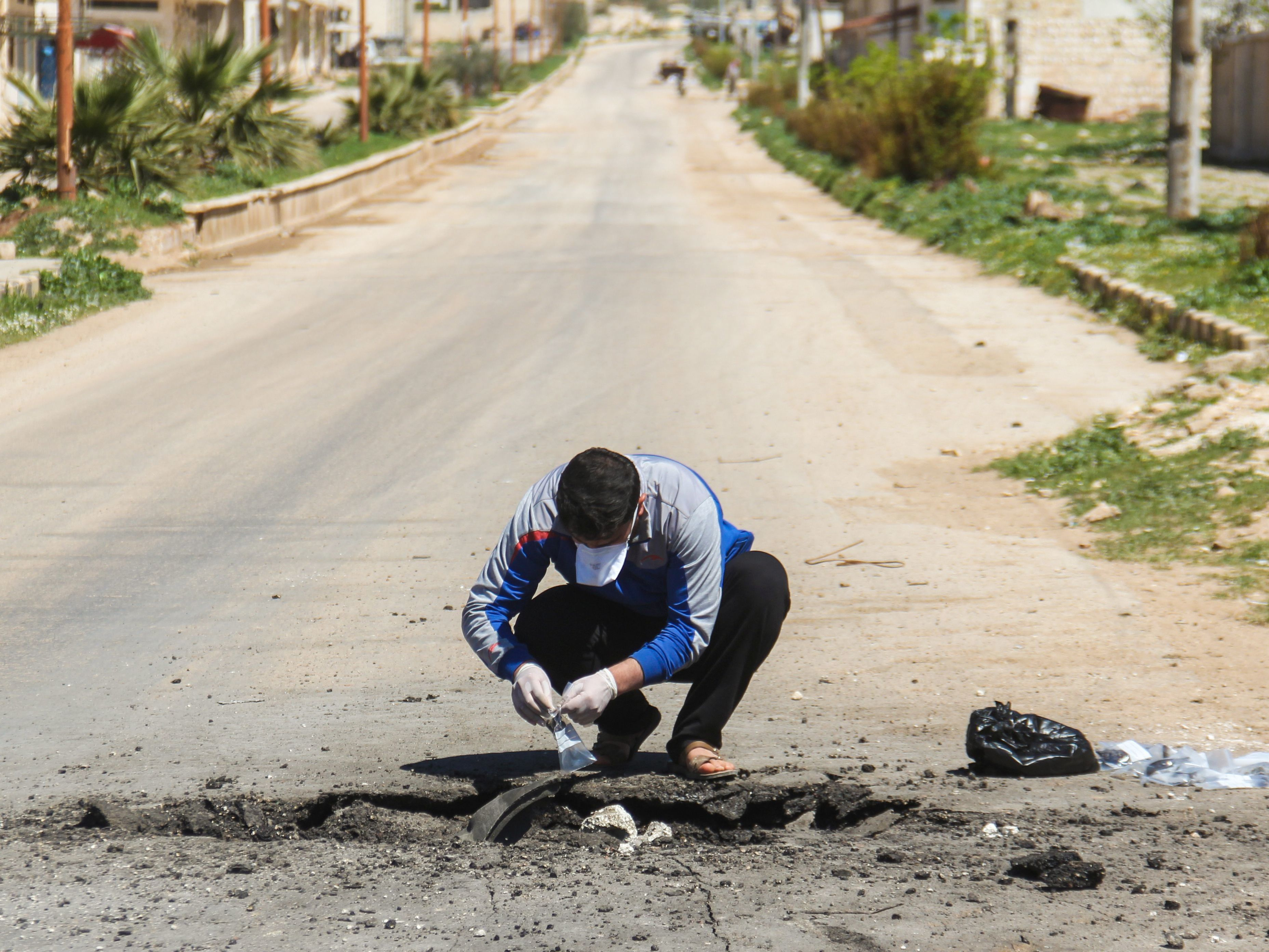 A man collects samples Wednesday from the site of a suspected toxic chemicals attack in Khan Shaykhun the day before. (Omar Haj Kadour/AFP/Getty Images)